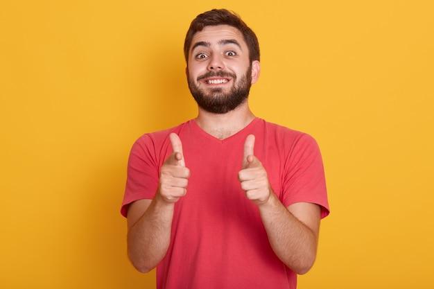 Изображение красивого усмехаясь современного человека одевает красную вскользь футболку показывая одобренный знак с обоими большими пальцами руки, модельный представлять изолированный на желтом, бородатом молодом мужчине с счастливым выражением лица.