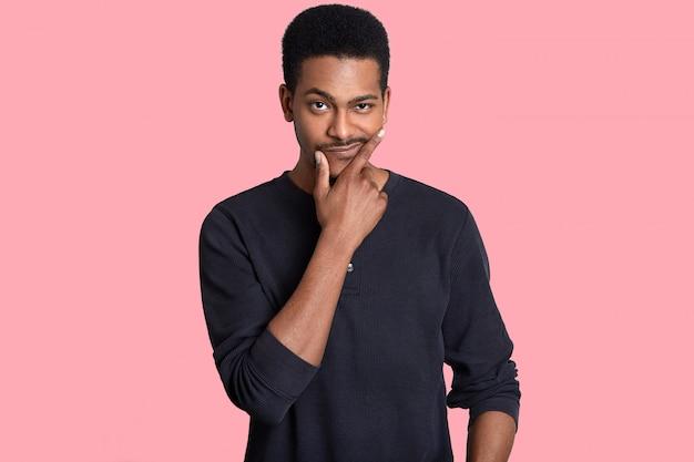 魅力的な黒人男性はあごを抱え、困惑して見え、眉を上げ、問題の必要な解決策を見つけようとし、ピンクの背景に分離されたカジュアルなジャンパーを着ています。人、考え、決断