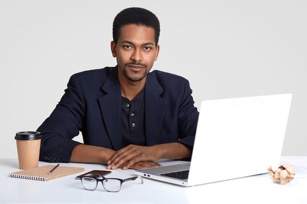 自信に満ちた表情で深刻な男性従業員、フォーマルな服を着て、フリーランスの作品、白いスタジオの壁に分離されたポータブルラップトップコンピューターでプロジェクト作業を準備します。