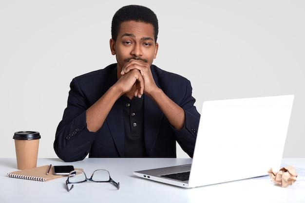 眠い疲れた豊かな男性のビジネスオーナーの写真はあごの下に手を保つ、収益を上げるための新しい戦略を開発する必要がある、正式な服装、ラップトップコンピューターと携帯電話を使用して白い壁に分離