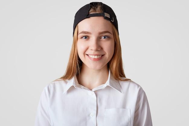 Милые милые девушки с позитивной улыбкой, в белой элегантной рубашке и стильной кепке, ходят в школу или колледж в хорошем настроении. хипстер девушка проводит время с друзьями
