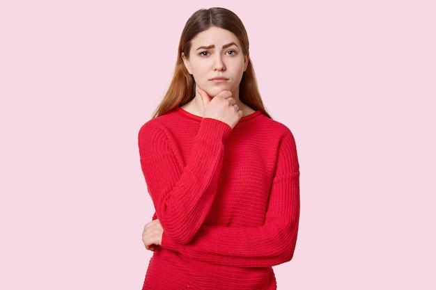 若い女性は胸に部分的に交差した手を持ち、悲しそうな表情で見え、濃い眉を上げ、赤い服を着て、バラ色に立っています。悲しい女性モデル