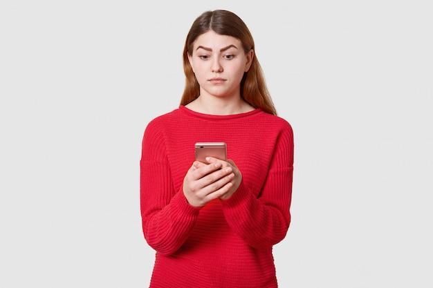 暗いストレートの髪と混乱しているかわいい女性、赤いセーターを着て、携帯電話を手に持って、白で隔離され、そのディスプレイを見てください。人々の感情の概念。
