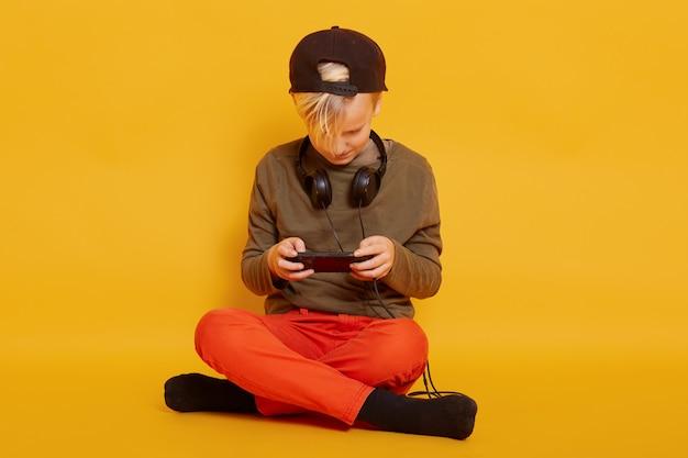 黄色の壁に分離された胡坐で床に座っている少年の肖像画を間近します。スマートフォンでオンラインでビデオを見たり、ゲームをしたりします。幼年期および技術の概念。