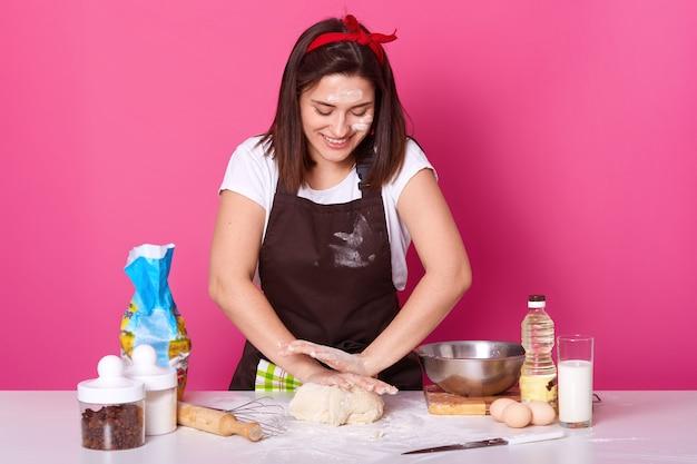 Студия выстрел из очаровательны девушки замешивать тесто руками на кухонном столе