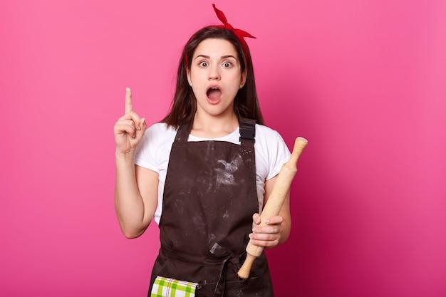 Крытый снимок занятой творческой домохозяйка позирует с кухонным оборудованием в одной руке