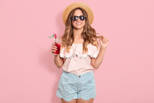 夏のブラウス、青の短い、黒いサングラスとガラスを保持している麦わら帽子の美しい若い女性