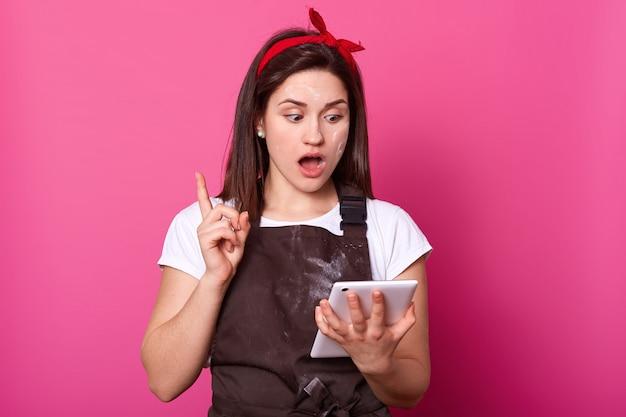 Домохозяйка женского повара, одетый в коричневый фартук, белая майка.