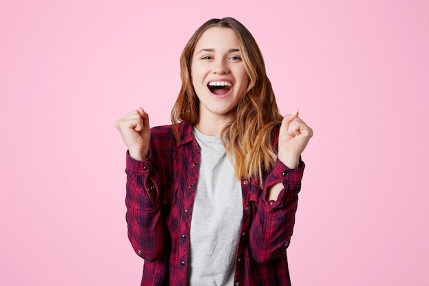 Поднимите портрет счастливой женщины в клетчатой рубашке, сжимает кулаки, радуется большим успехам и целям достижения