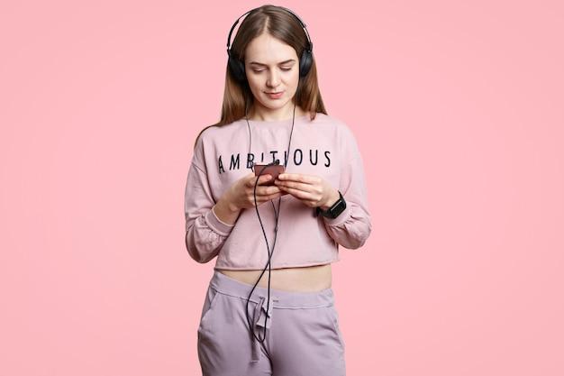 Красивая серьезная молодая женщина держит современный сотовый телефон, наслаждается музыкой в наушниках в плейлисте