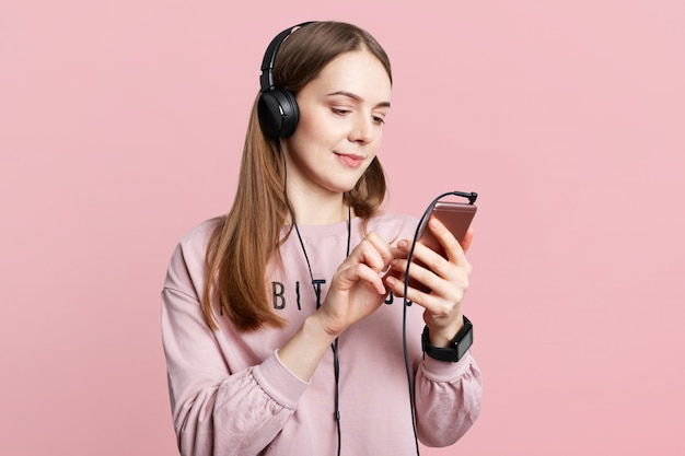 見栄えの良い女性のスタジオショットは、携帯電話でオンラインでニュースを読むか、ヘッドフォンでビデオを見る