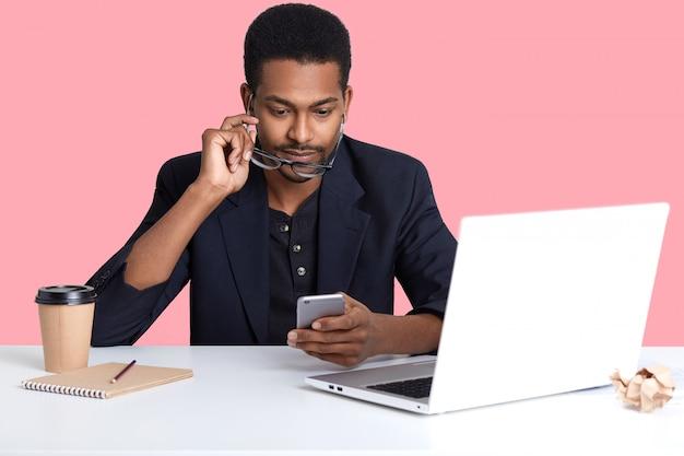 彼のスマートフォンでアフリカ系アメリカ人の実業家チェックメールの肖像画を間近します。