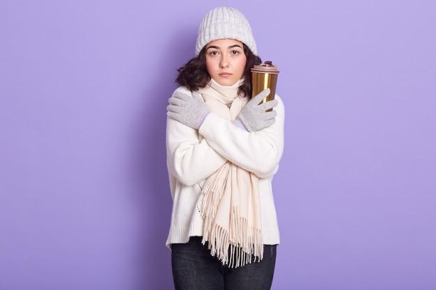魅力的な若い黒髪の女性が寒さに震え、自分を熱しようとし、温かい飲み物とサーマルマグを持っている