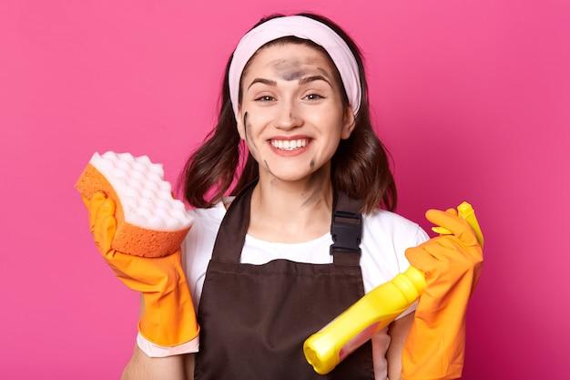 Веселая энергичная яркая молодая женщина выглядит счастливым, изолированных на розовый в студии, готовы сделать генеральную уборку