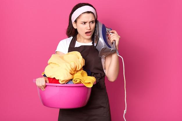 感動した疲れた主婦、洗面台を衣類とアイロンで保持し、それで顔に触れた