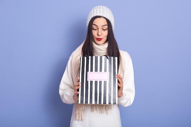 Фото любопытно удивлен молодая самка держа бумажный мешок в обеих руках, глядя внутрь