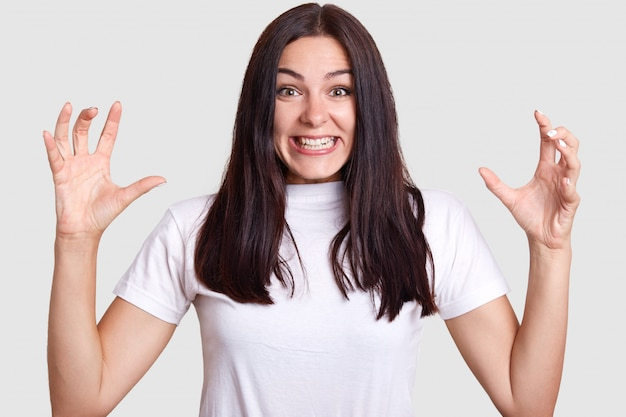 Очень эмоциональный человек, женщина с темными волосами и большими карими глазами без макияжа пытается показать свой характер