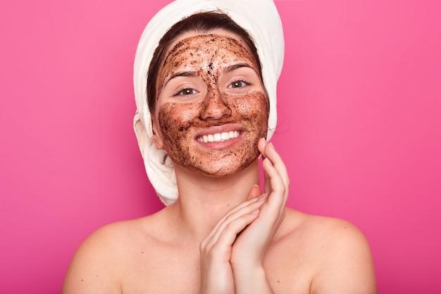 彼女の頭に白いタオルを持つ若い女性は裸の体、ピンクの壁に笑みを浮かべてポーズ、顔の近くに折り畳まれた手のひらを保持