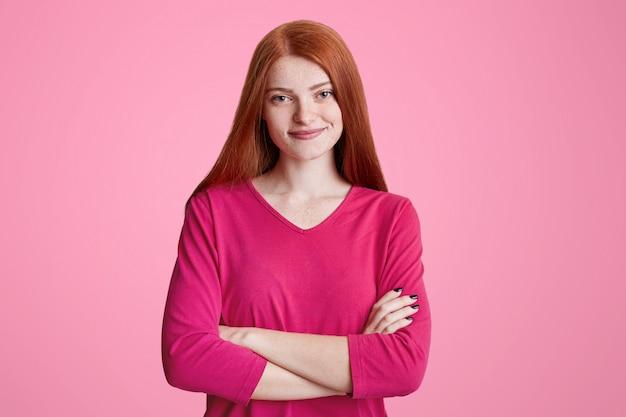 長い生姜髪のかわいいそばかすのある女性は、手を組んで立って、ピンクのセーターを着ており、友達と会えて嬉しい