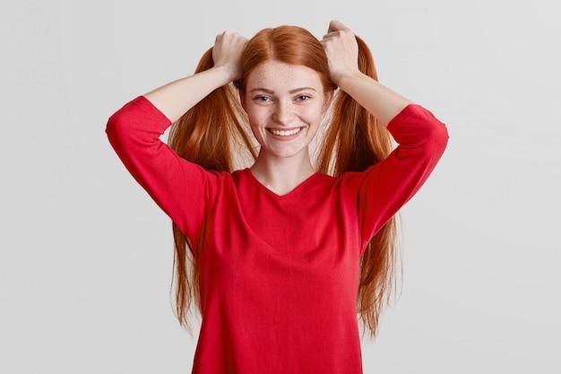 ポジティブな赤毛のそばかすのある女性は長い髪をし、ポニーの尻尾を作り、カメラでポーズをとって満足し、赤いカジュアルセーターを着ています。