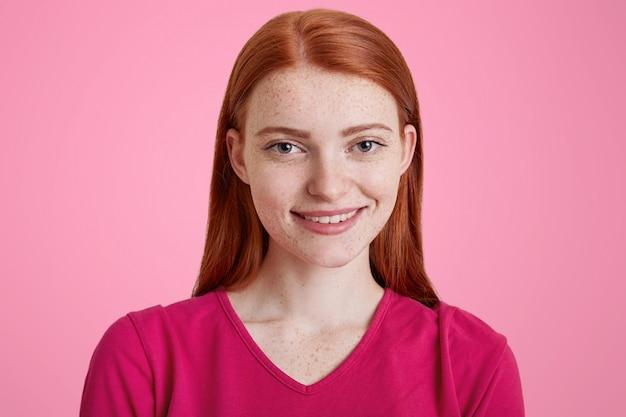 心地よい笑顔の生姜の女性、そばかすのある肌、写真撮影に喜んでいる、ピンクのセーターを着ている女性
