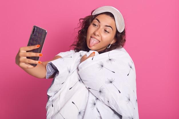 Крупным планом портрет счастливой женщины завернутый в белое одеяло с одуванчиком, показывая ее язык, делая селфи