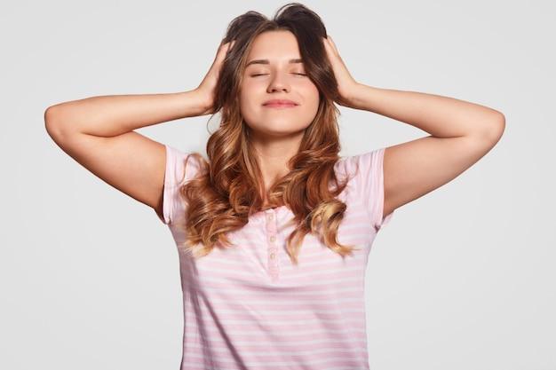 Довольная переутомленная молодая женщина держит обе руки на голове, глаза закрыты, одета в повседневную ночную одежду, приятно улыбается