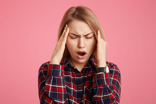Усталость, стресс, молодая модель женского пола держит руки на голову, закрывает глаза и открывает рот в отчаянии