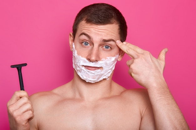 Крупным планом портрет красавец с пеной для бритья на лице, держит бритву в руке для бритья
