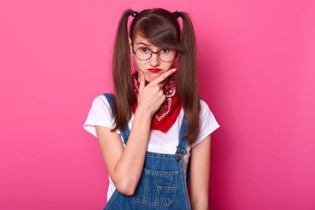幼稚なカリスマ的な若い女性は、彼女の計画を考えて顔に手を置き、顔をしかめます