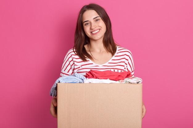 Счастливый женский позирует, изолированных на розовом фоне, держа картонную коробку с одеждой многоразового использования, одежда для бедных людей