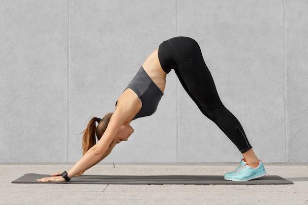 Самостоятельно определяющая фитнес женщина делает спортивные упражнения на коврике в тренажерном зале, стоит на руках, одета в майку и леггинсы