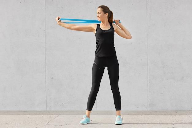 Снимок спортивной молодой женщины, одетой в черную одежду, растягивает руки с резинкой, хочет иметь мышцы, обладает хорошей гибкостью