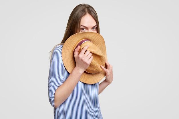 暗いストレートの髪の面白い女性は麦わら帽子の後ろに隠れる、白で分離されたスタイリッシュなブラウスに身を包んだ楽しい