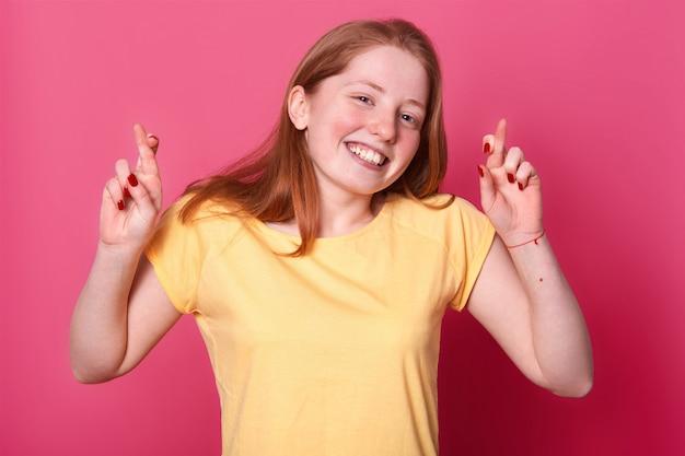 Портрет желанной молодой женщины в повседневной желтой футболке, с каштановыми волосами, скрещивающими пальцы, надеется на важное событие