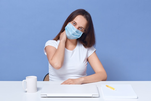 Горизонтальный снимок женщины, работающей на ноутбуке дома, леди, имеющая дистанционную работу, позирует на столе, изолированных на синий