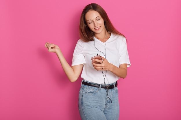 スマートフォン経由で音楽を聴くイヤホンで踊る女性。自由な時間を過ごす遊び心のある幸せな笑顔若い、魅力的な女性