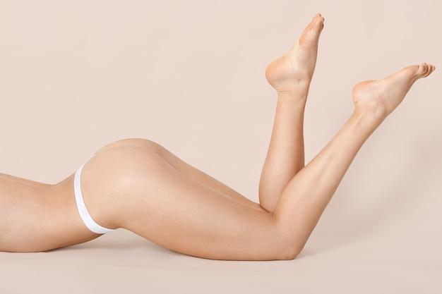 スリムな女性が彼女の足を上げる