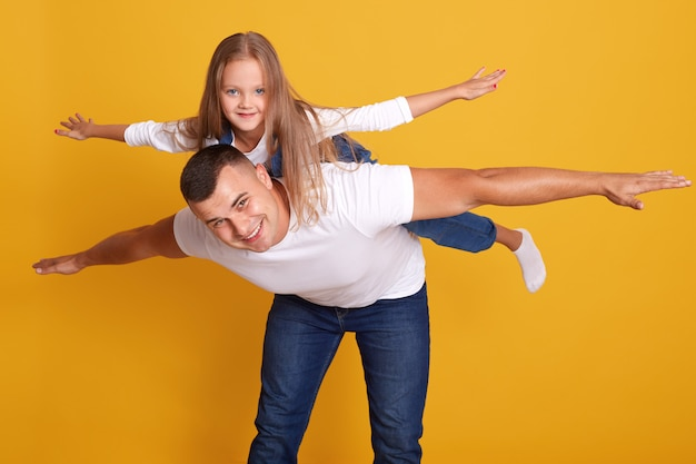 Счастливый отец, давая его дочь контрейлерных перевозок, папа и ребенок, весело вместе, счастливая семья.