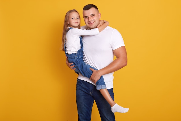 彼女の父親、ハンサムな男の手で子供を抱いて、カジュアルな服を着て魅力的な子供女の子のスタジオ撮影