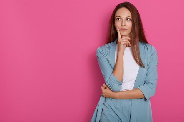 Молодая женщина думает и размышляет над чем-то с ее пальцем на подбородке, глядя в сторону с задумчивым выражением лица