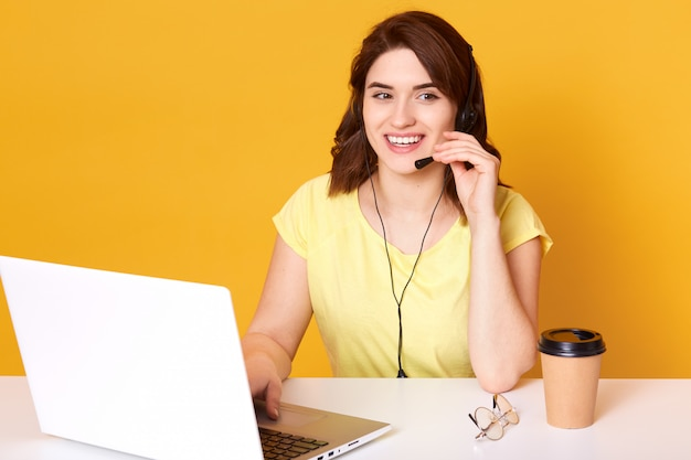 Половина длины фото женщины оператора, сидя на рабочий стол, глядя в сторону, касаясь гарнитуры, изолированных на желтый