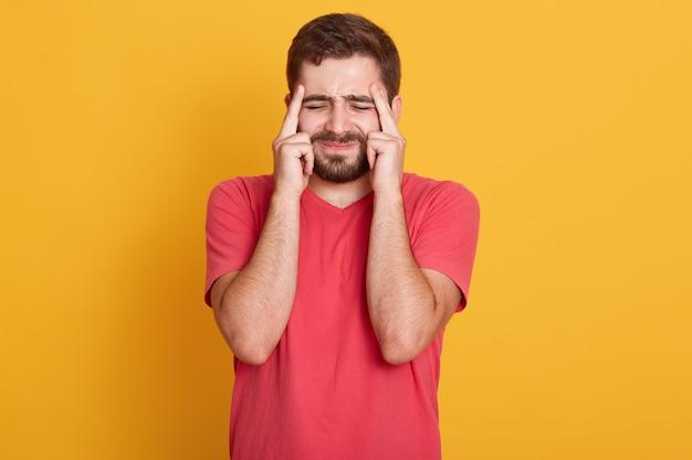 不快感のある男性の顔をしかめている顔の室内撮影。頭痛があり、疲れている、休息が必要、痛みで目を閉じて、こめかみに指を当てている