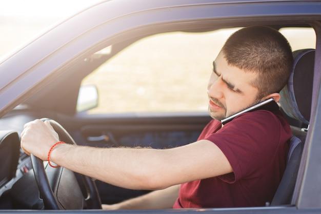 Водитель-мужчина с сосредоточенным взглядом водит машину и разговаривает по мобильному телефону, так как решает важные проблемы на расстоянии, путешествует на большие расстояния
