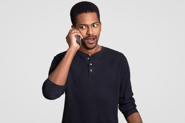 Смущенный афроамериканец имеет телефон, обсуждает что-то неприятное и удивительное, смущенно смотрит в сторону