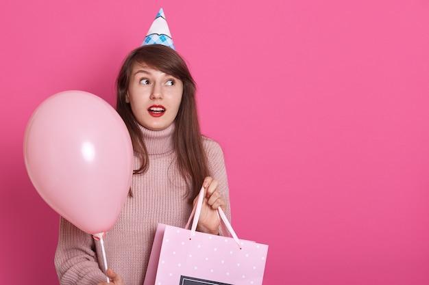Счастливая брюнетка с розовым воздушным шариком и подарком на день рождения в руках, держит рот открытым, в удивлении, смотрит в сторону с истощенным