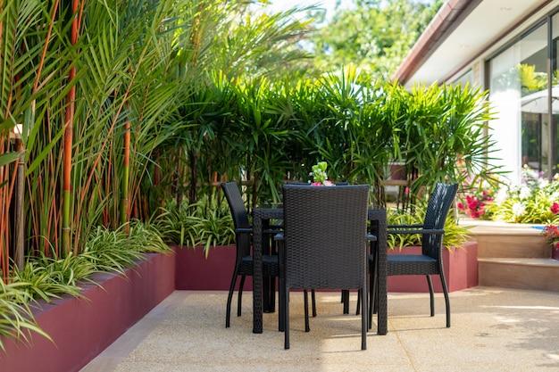家、家、ヴィラの外観デザインには、緑の植物に囲まれた庭に屋外のダイニングテーブルとダイニングチェアがあります。