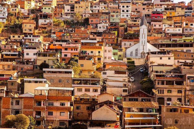 着色された家とミナスジェライス州-ブラジルの傾斜した都市の教会