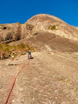 ブラジルの傾斜した岩壁を登るロッククライマー