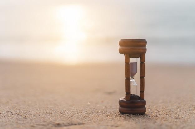 Малое время шоу песочных часов течет на предпосылке песчаного пляжа.